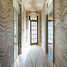 Horse Meadow country house master bedroom hallway with handpainted marble wallpaper, moroccan rug and capiz shell lights. The custom steel doors lead into the master bath.