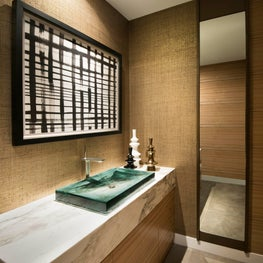 Powder room with natural wall finishes and glass sink