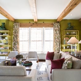 Family Room with green walls and rustic wood ceiling, door and window beams.