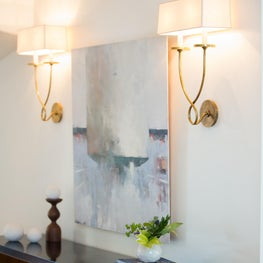 Waterfall hall table with brass sconces and modern art- by Sophia Shibles