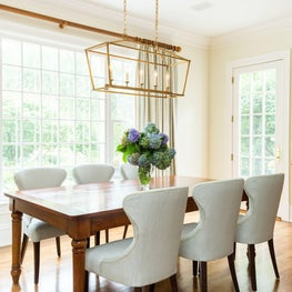 Kitchen Dining with Cherry Table, Elegantly Upholstered Dining Chairs, Brass Linear Chandelier from Circa and Linen Panel Drapery