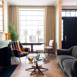 Eclectic Living Room with marble mantle, herringbone floors, & stripe chairs