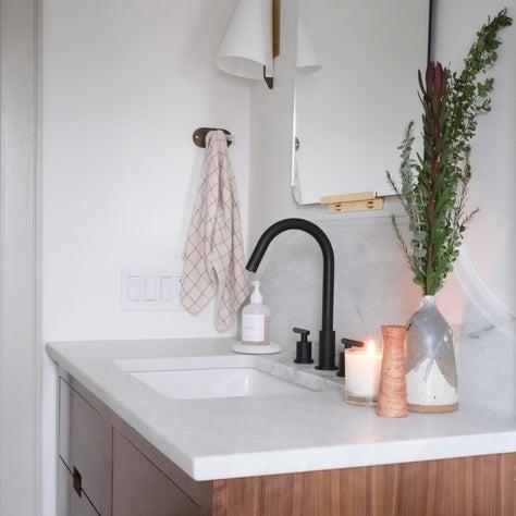 Warm modern bathroom with marble countertops, custom backsplash and walnut vanity
