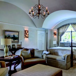 Oversized chairs and ottoman:custon sized sconces in vaulted ceiling bedroom
