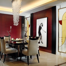 Inviting dining room with custom glass panels juxtaposed with modern artwork.
