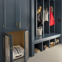 Custom indigo blue and brass dog kennel is home in this mudroom