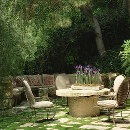 Rose Tarlow Melrose House Twig Iron Chairs placed around an old stone table.