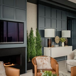 Living room with leather club chairs and paneled wall designed by Robin Gannon Interiors