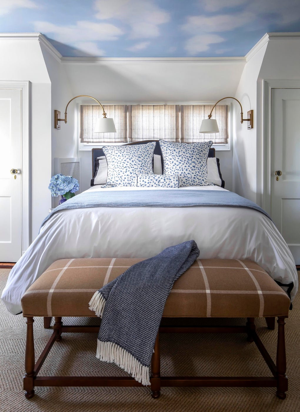 Blue and white bedroom with navy leopard linens, swing arm sconces, sheer roman shades and a wool camel plaid bench with throw.
