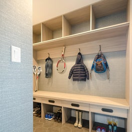 High Trafficked Mudroom for a Busy Family, with Textured Wallpaper, Black Hardware, and Hexagonal Floor Tiles