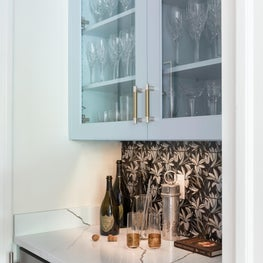 Custom bar with floral tile, bespoke cabinets, and wine fridge detail