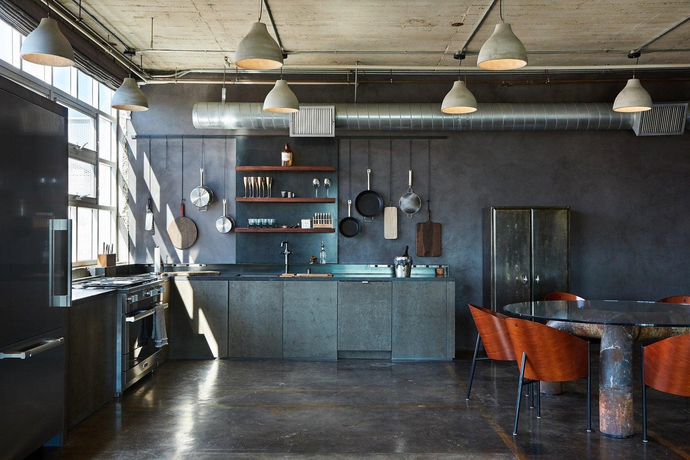 Matte black kitchen counters of Honed Petit Granite & blackened steel backsplash