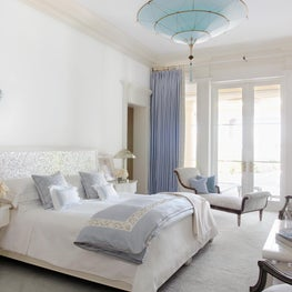 Master suite with French doors and a Fortuny chandelier, mother-of-pearl headboard; bed and side tables designed by John Meeks