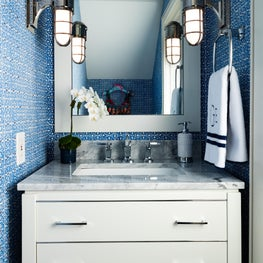 Crisp blue walls create a liveliness to this white powder room.