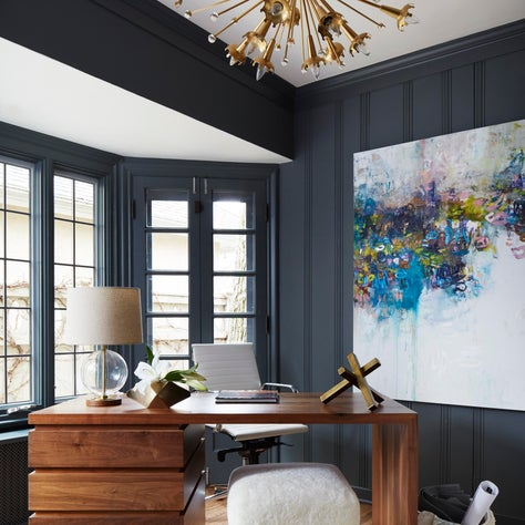 Home Office with with dark gray paint, art and brass chandelier