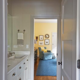 Jack & Jill bathroom with yellow and blue nursery, marble mosaic floor, white