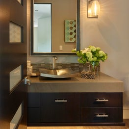 Powder Bath with floating vanity lit from below and hammered metal vessel sink