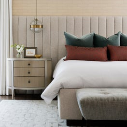 Neutral-toned master bedroom with tufted headboard and brass details