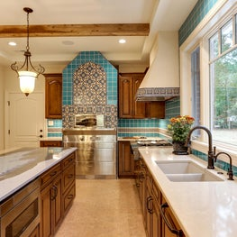Mediterranean kitchen with hand-crafted Spanish tile, wood beams, and pizza oven