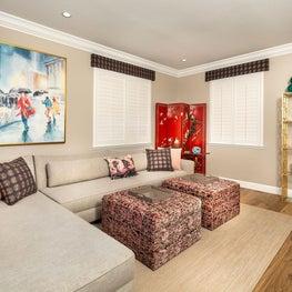 Bold patterns, bright custom ottomans and sofa pillows, comfortable media room loft