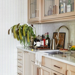 High-gloss painted cabinetry in bar with marble countertop and wallpaper