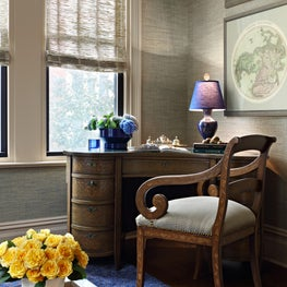Handsomely framed maps hang above a beautiful French floral patterned intarsia curved desk
