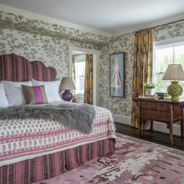 Bedroom with Upholstered Headboard, Pink Rug and Textured Throw