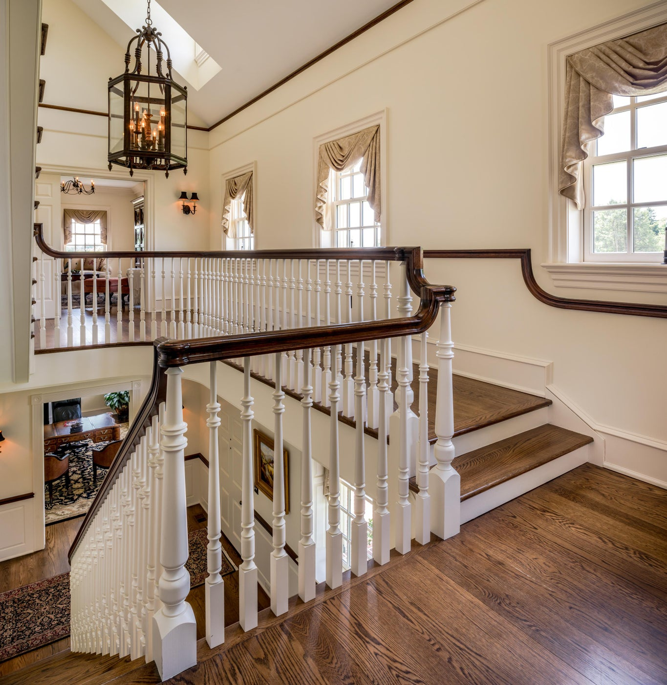 Traditional open and bright Staircase with wrought iron hanging light fixture