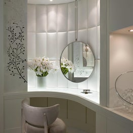 A neutral vanity is dramatized by a French mirror on custom leather panels.