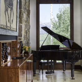 Mountain home living room with side bar and grand piano.