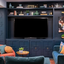 A Mid-Century Country Club inspired basement media room with rich blue built-in storage.