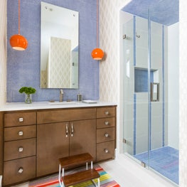 Kids bathroom featuring penny round tiles and fun orange pendant lights