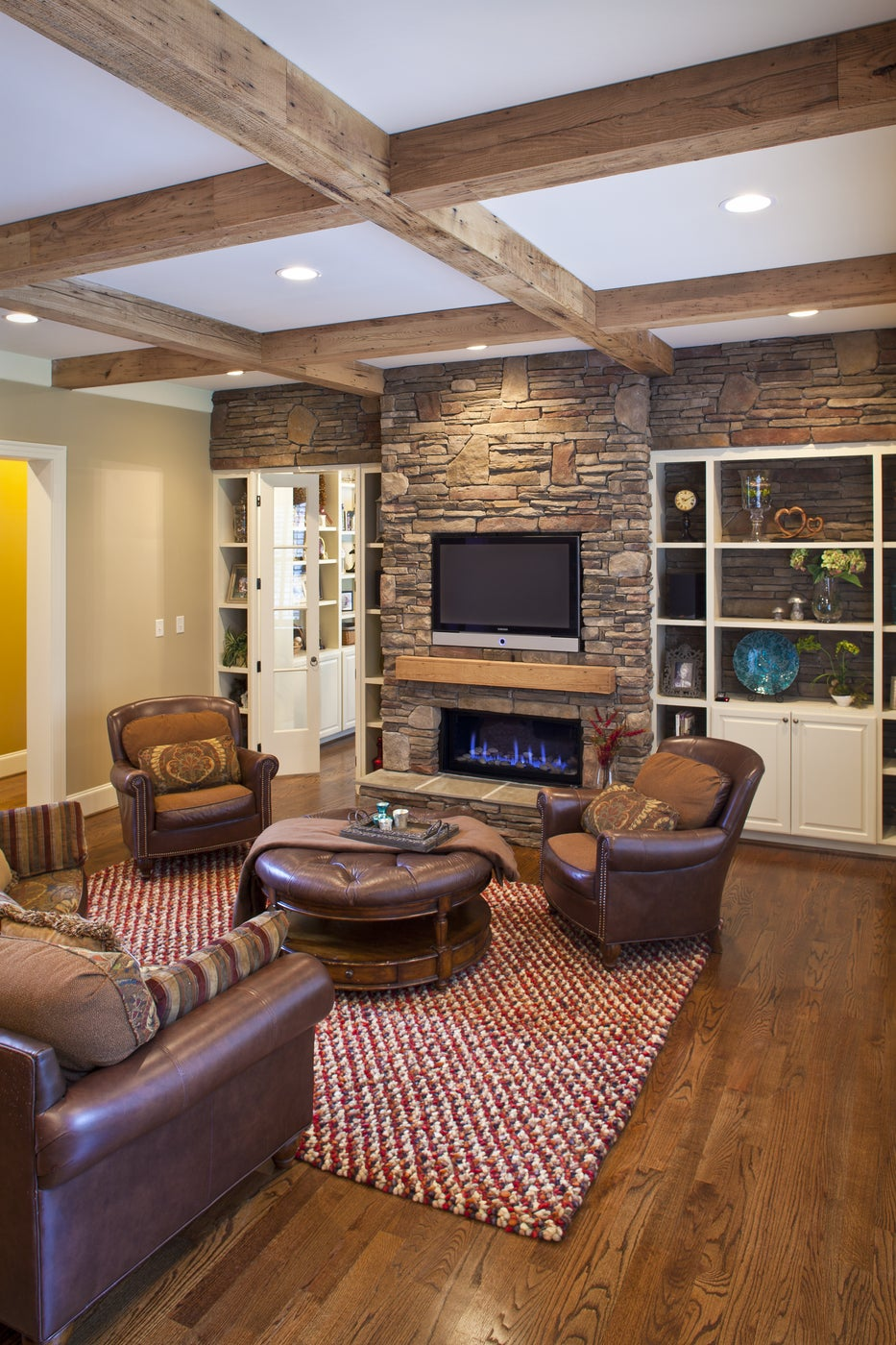Cozy living room with reclaimed wood beams and mantel, and stone fireplace wall