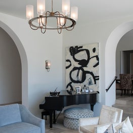 Modern Mediterranean estate with abstract art and luxe Urban Electric Company lighting.