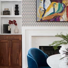 White kitchen with marble fireplace, walnut cabinetry, geometric wallpaper, oversized artwork, blue dining chairs and marble dining table