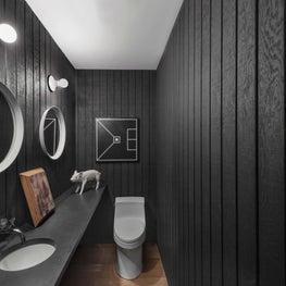 Sleek bathroom with black paneled walls, lightbulb sconces, round mirrors