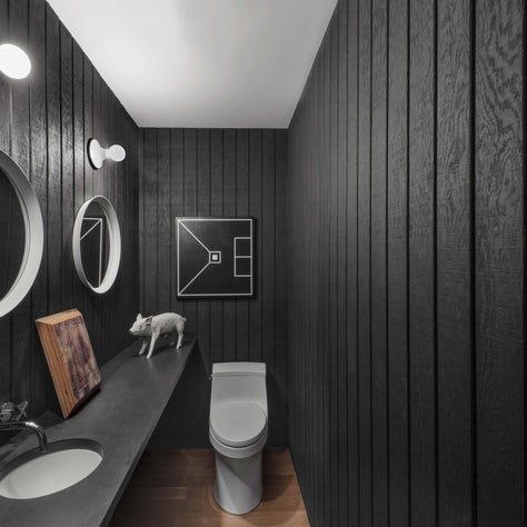 Sleek bathroom with black paneled walls, lightbulb sconces, round mirrors