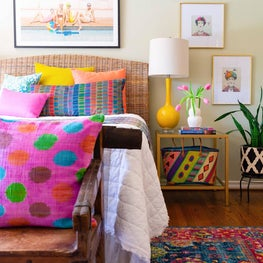 Bedroom with colorful rugs and pillows