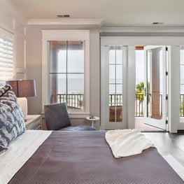 A serene bedroom suite with beachfront views and inspired palette