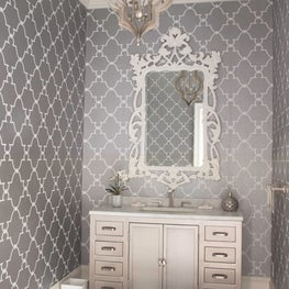A glamorous powder room with ornate mirror and custom metallic vanity.