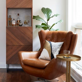 Bar nook, bar lounge with leather chair, walnut bar cabinet, large windows, brass accents