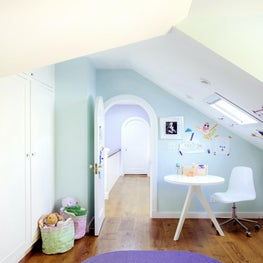 Children's room with pale blue accent walls, skylight, playful ceiling angles