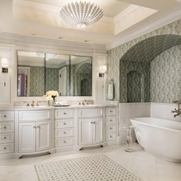 This master white bathroom has one wall with a green patterned wallpaper creating a tropical vibe.