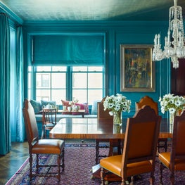 Turquoise blue dining room with traditional furniture and rug