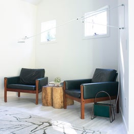East Hampton Master Bedroom with Vintage Green Leather Wegner Lounge Chairs and Rug Company Rug