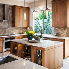 Contemporary kitchen with quartzite countertops, stainless accents, glass splash