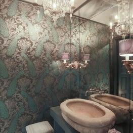 Formal powder- reclaimed stone sink, metallic wallpaper & antique mirrored wall