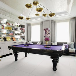 Billiard room with a Stilnovo chandelier, which doubles as a sculpture and breaks away from the style of traditional poolroom lighting fixtures