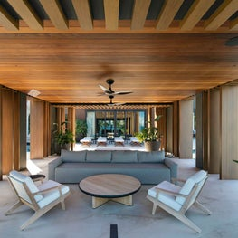 Outdoor seating area with wood paneled ceiling and beamed.