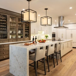 This renovated custom white kitchen features a dark wood builtin which softens the ambiance.
